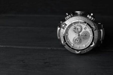 Stainless steel wristwatch on a dark wooden background.