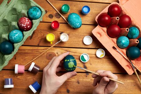 Happy Easter! Woman's hands paint eggs for Easter day. Preparing for Easter. Top view.