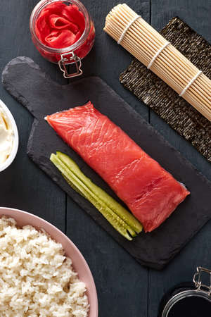 Pink salmon on a stone serving board with cucumbers, philadelphia cheese, dyed ginger, nori leaf, soy sauce and freshly cooked rice. Top view of ingredients for making sushi rolls.