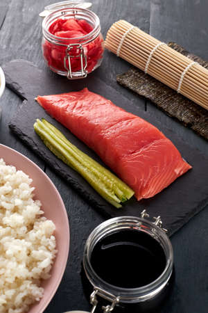 Pink salmon on a stone serving board with cucumbers, philadelphia cheese, dyed ginger, nori leaf, soy sauce and freshly cooked rice. Ingredients for making sushi rolls.