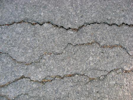 Texture of cracks on asphalt background  photo