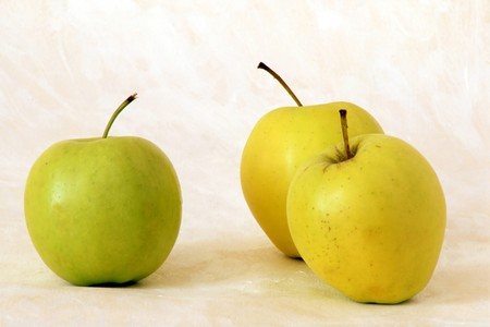 Three yellow apples on painted background photo