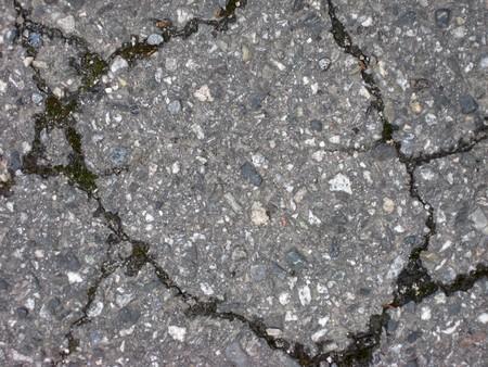 Cracks on asphalt background closeup photo