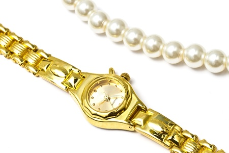 Woman golden wrist watch and pearl necklace isolated on white background   photo