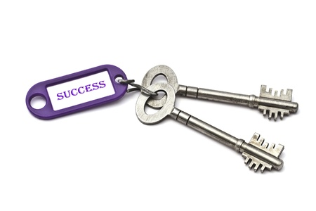 Key with a success tag closeup on white background photo
