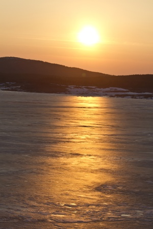 Beautiful landscape of sunset over frozen lake and mountain photo