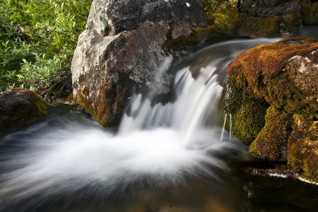 Flowing water of beautiful mountain stream photo