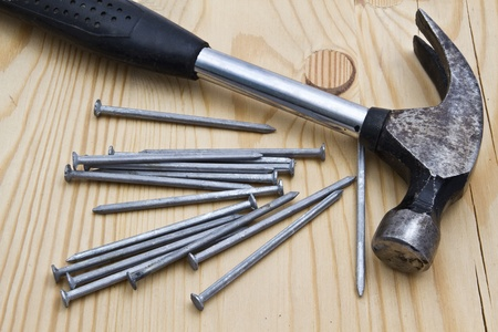 Old hammer and nails on wood background Stock Photo - 10315300