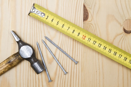 Old hammer , tape measure  and nails on wood background   photo