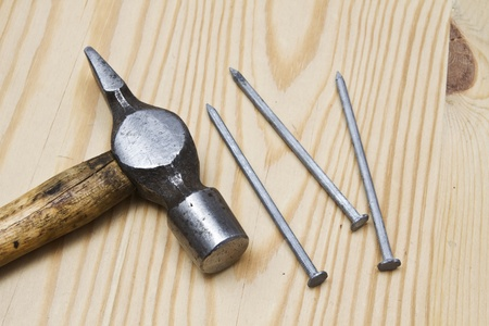 Old hammer and nails on wood background   photo
