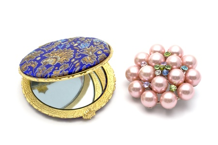 Beautiful cosmetic mirror iand brooch closeup photo