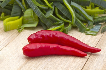 Fresh leek and red chili pepper on wood background photo