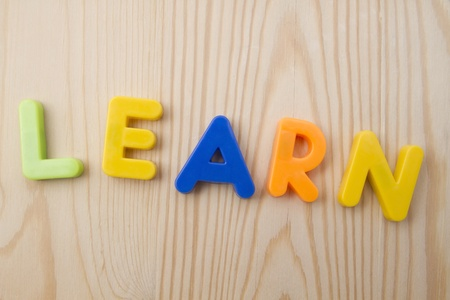 learing: Letter magnets LEARN closuep on wood background Stock Photo