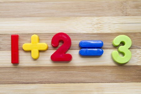 Math example with numbers magnets on wood background
