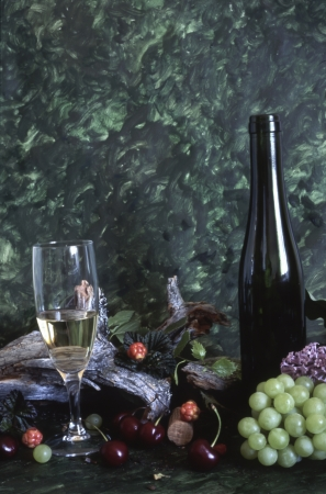 Wine bottle and grapes isolated on painted background  photo