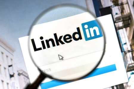 network: Linkedin website under a magnifying glass. Linkedin is a business oriented social networking website.