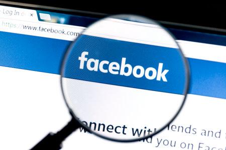 拡大鏡で Facebook のウェブサイト。Facebook は世界で最も訪問されたソーシャル ネットワークです。 報道画像