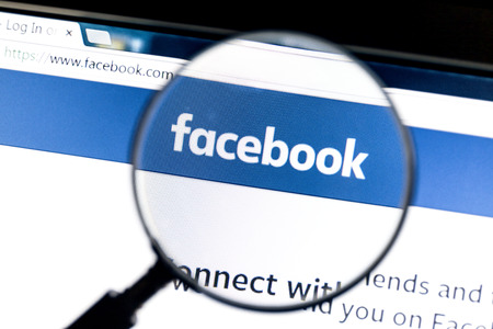 Facebook website under a magnifying glass. Facebook is the most visited social network in the world Editorial