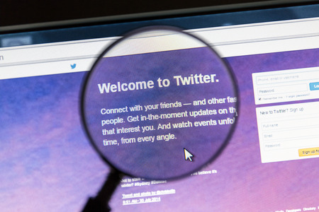 Twitters website under a magnifying glass. Twitter is an online social networking service that enables users to send and read short messages called tweets.