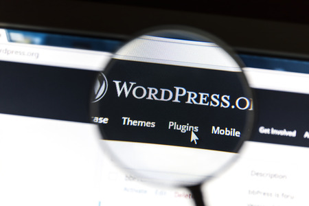 Close up of Wordpress website under a magnifying glass. WordPress is a free and open source blogging tool.