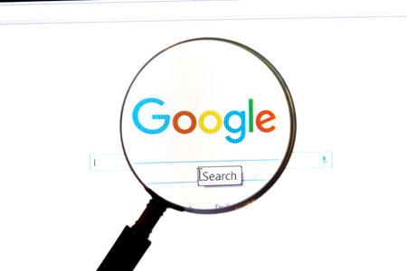 拡大鏡で Google のウェブサイト。Google は世界で最も人気のある検索エンジンです。