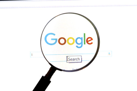 Google website under a magnifying glass. Google is the world's most popular search engine