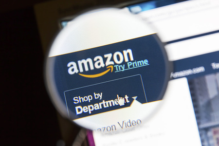 bidding: Closeup of Amazon website under a magnifying glass. Amazon is an american electronic commerce and cloud computing company