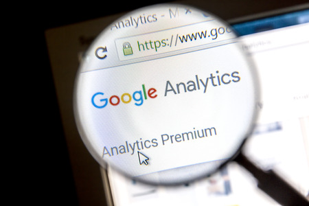 Google analytics website under a magnifying glass.. Google Analytics is a service offered by Google that generates statistics about a websites traffic. Editorial