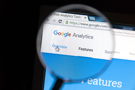 Google Analytics website under a magnifying glass. Google Analytics is a web analytics service offered by Google
