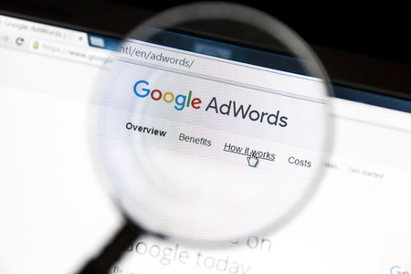 Google Adwords website under a magnifying glass. Google AdWords is an online advertising service. Stock Photo - 57066618