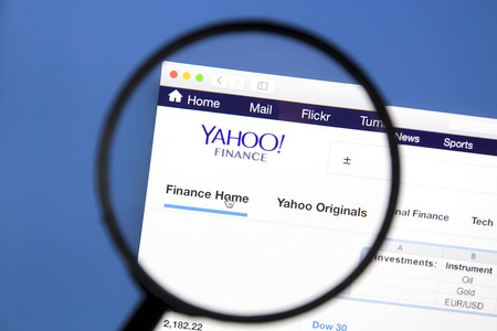 web portal: Yahoo finance website under a magnifying glass Editorial