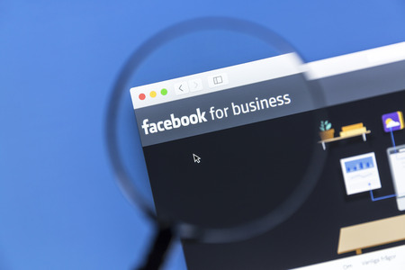 Closeup of Facebook Business website under a magnifying glass. Facebook is the most visited social network in the world Redakční