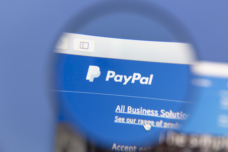 paypal: PayPal homepage under a magnifying glass. PayPal is an online payments system Editorial