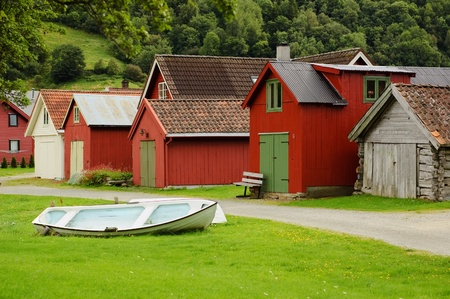 Countryside view of coloured wooden buildings and the boat lying on a lawn photo