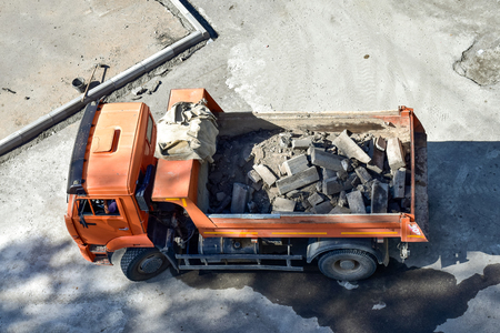 Heavy industrial dump truck .City road construction and renewal site. Dump truck replaces curbs on the roads. Almaty, Kazakhsatan