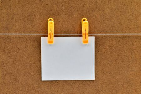 Blank white sticker that hangs with a clothespin on a rope on a brown background of chipboard