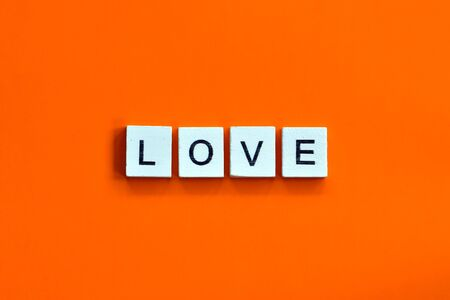 A homemade wooden tile with letters on a orange background, word love