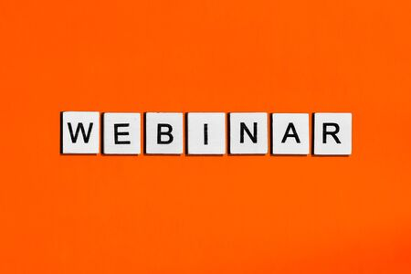 A homemade wooden tile with letters on a orange background, word webinar