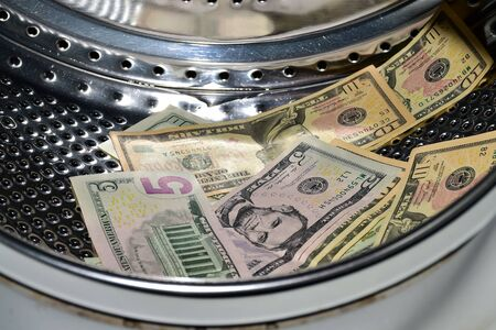 Banknotes in the washing machine, money laundering. Process of making illegally-gained proceeds (dirty money) appear legal (clean)