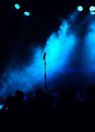 empty blue stage, microphone in the center, silhouette of audience, lights  Stock Photo