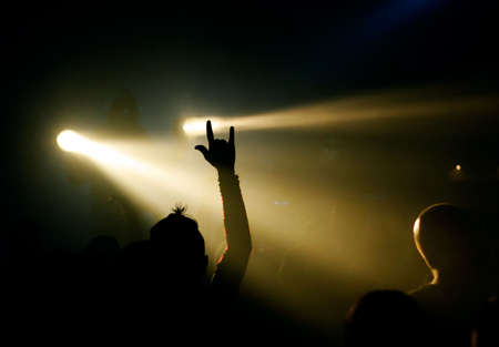 music fan showing devils sign, yellow light in the background Stock Photo