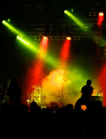 crossed red and green light, yellow fog with hidden drummer, black silhouette of vocalist and audience