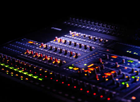 mixer or mixing concole in the dark, with blurry lights and controllers Stock Photo