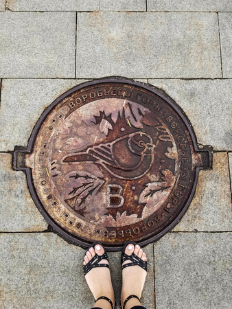 Girls feet stand on sewer manhole on Vorobyovy Gory. Bird on hatch is a sparrow - symbol of place.