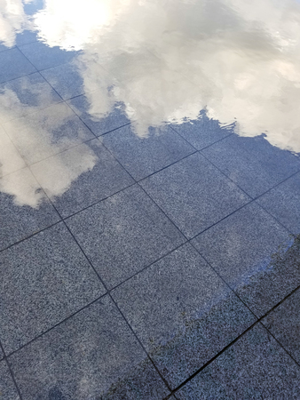 Sky and clouds reflected in puddle on the floor.