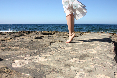 Legs of young girl in white fluttering skirt stand tiptoe on stone beach