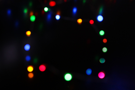 Frame of many shiny colorful bokeh circles on black. New year abstract blurred background