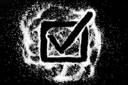 Checking mark symbol with long tail in checkbox drawing by finger on white snow salt powder spot cloud in center on black background. Tick concept with place for text. Copy space.