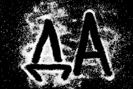 Yes word in russian language DA symbol drawing by finger on white snow salt powder on black background. Capital letters