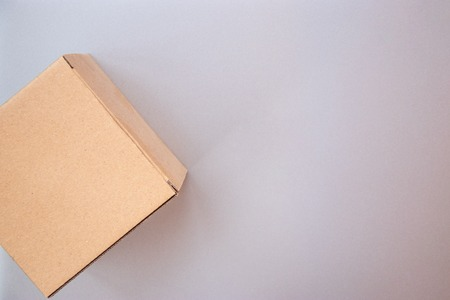 Corner of closed big square cardboard craft gift box on the silver gray metal background Stock Photo
